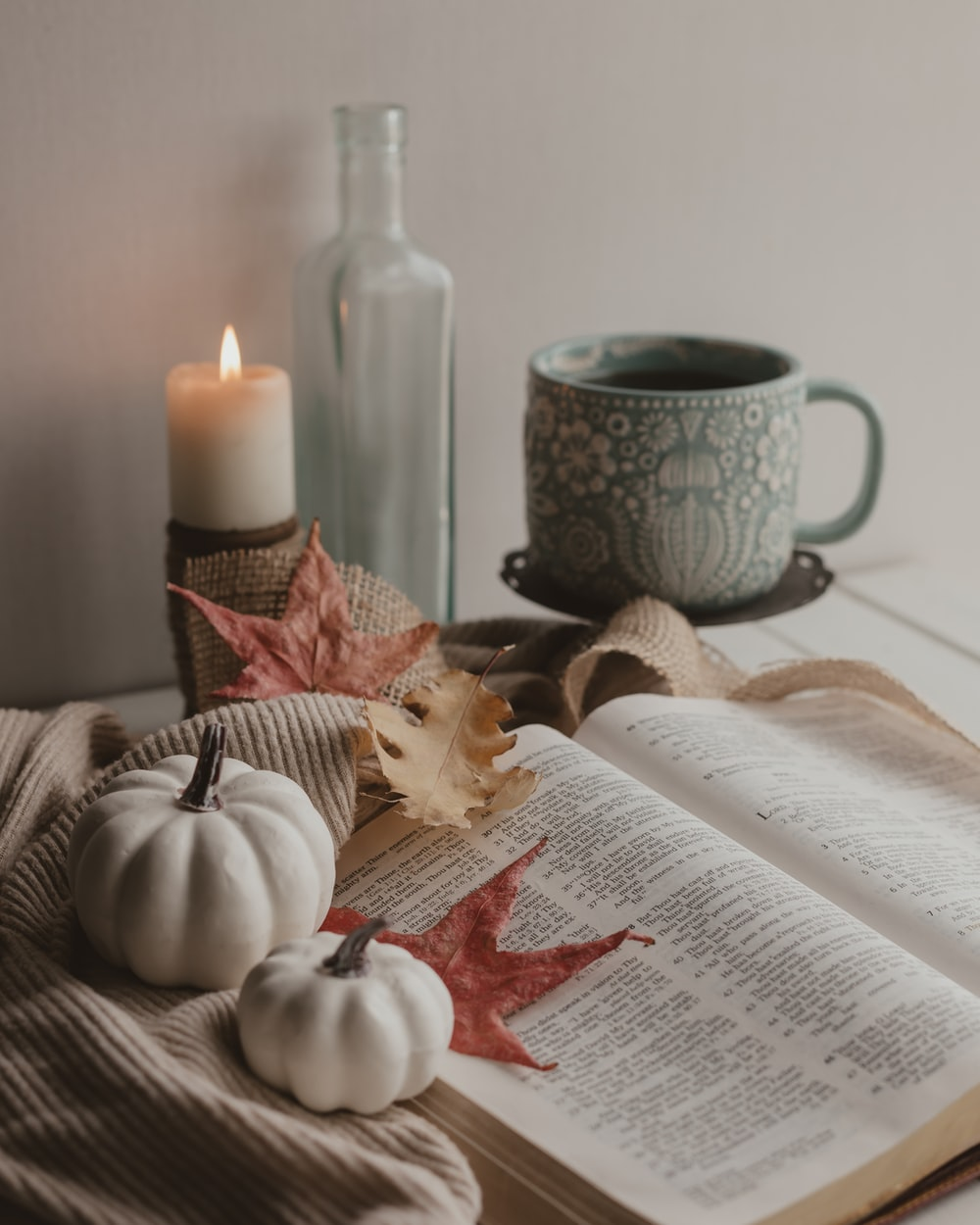 white candle beside white book page