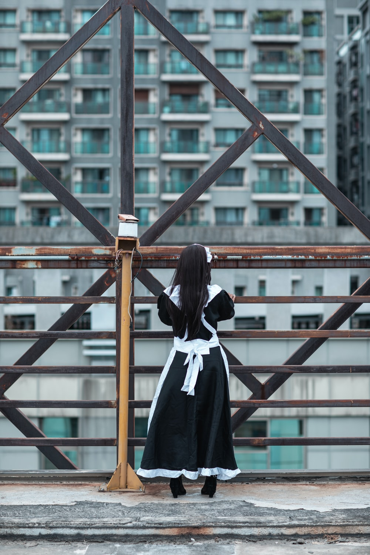 woman in black and white school uniform standing on brown wooden bridge