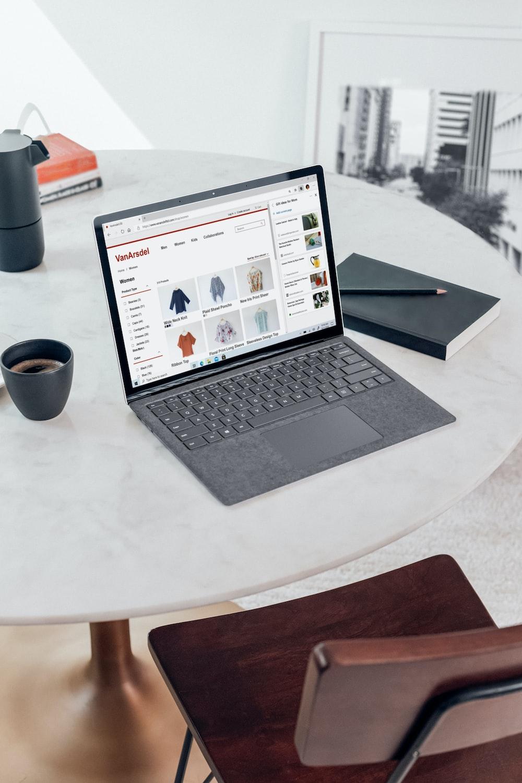 black laptop computer on white round table