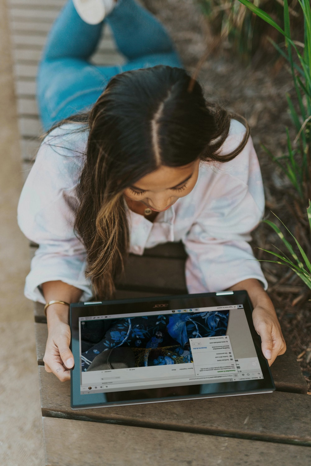 woman in white long sleeve shirt holding laptop