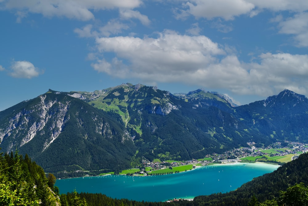 green and gray mountains beside body of water under blue and white cloudy sky during daytime