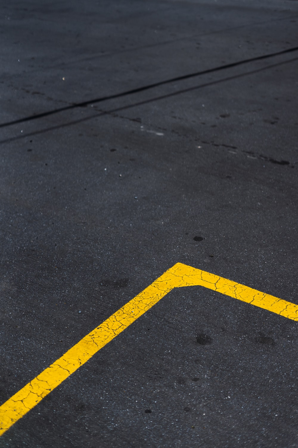 yellow and black arrow sign on gray concrete road