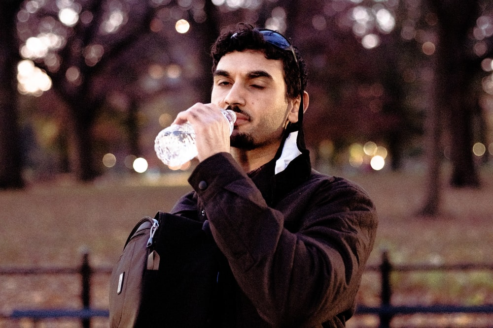 man in black jacket drinking water