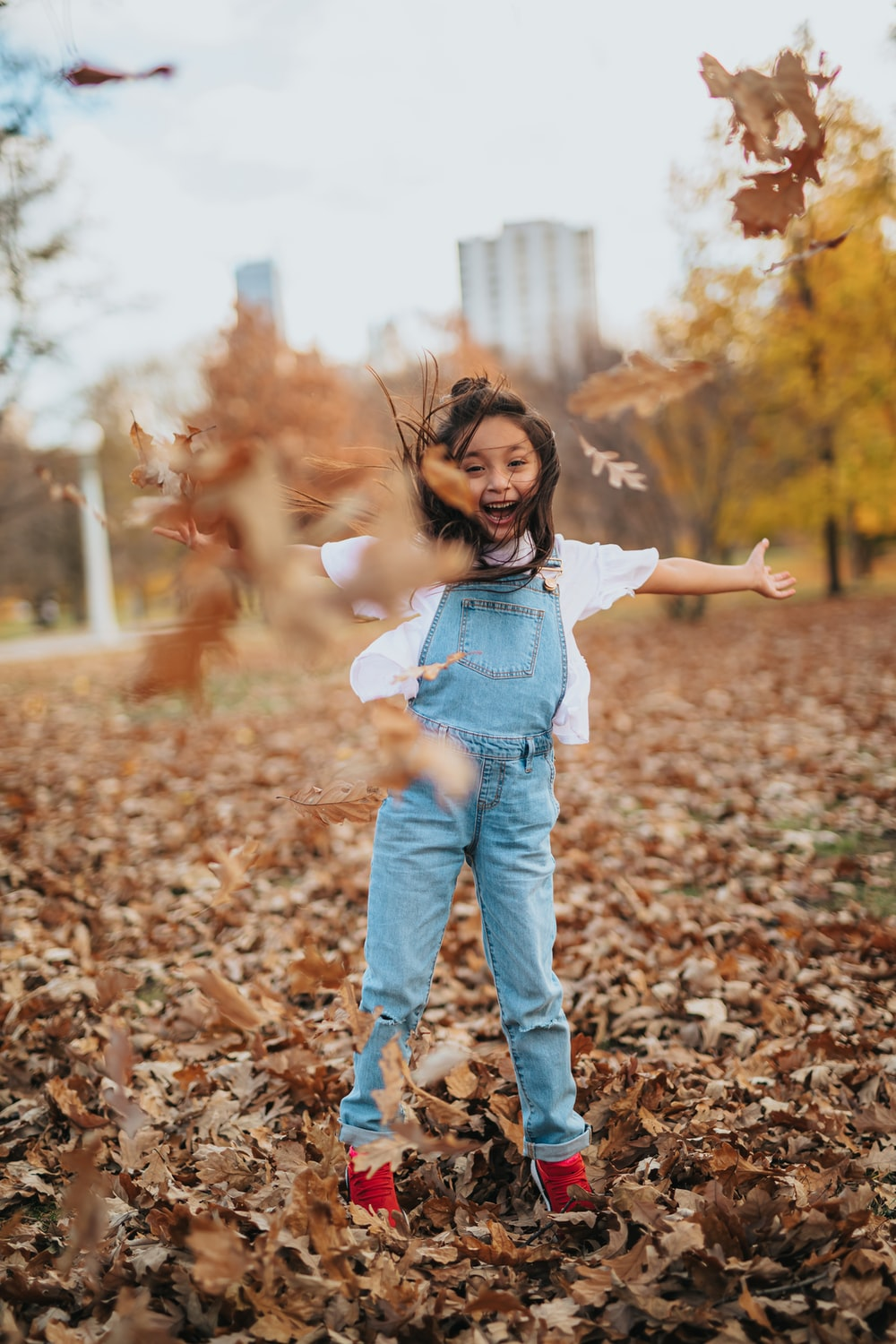 girl in blue denim jacket and blue denim jeans standing on dried leaves during daytime