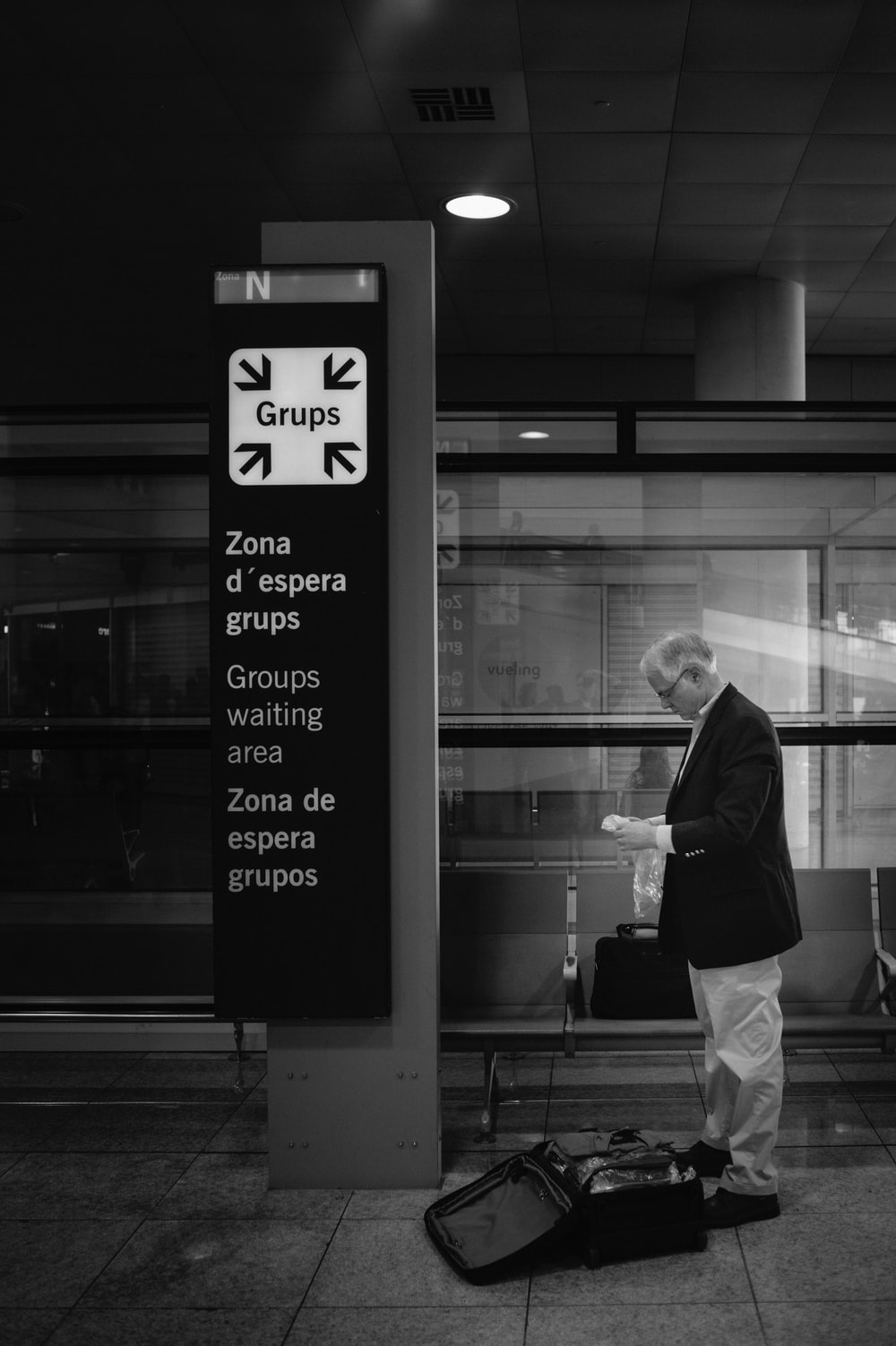 grayscale photo of man in black jacket and white pants standing beside glass window
