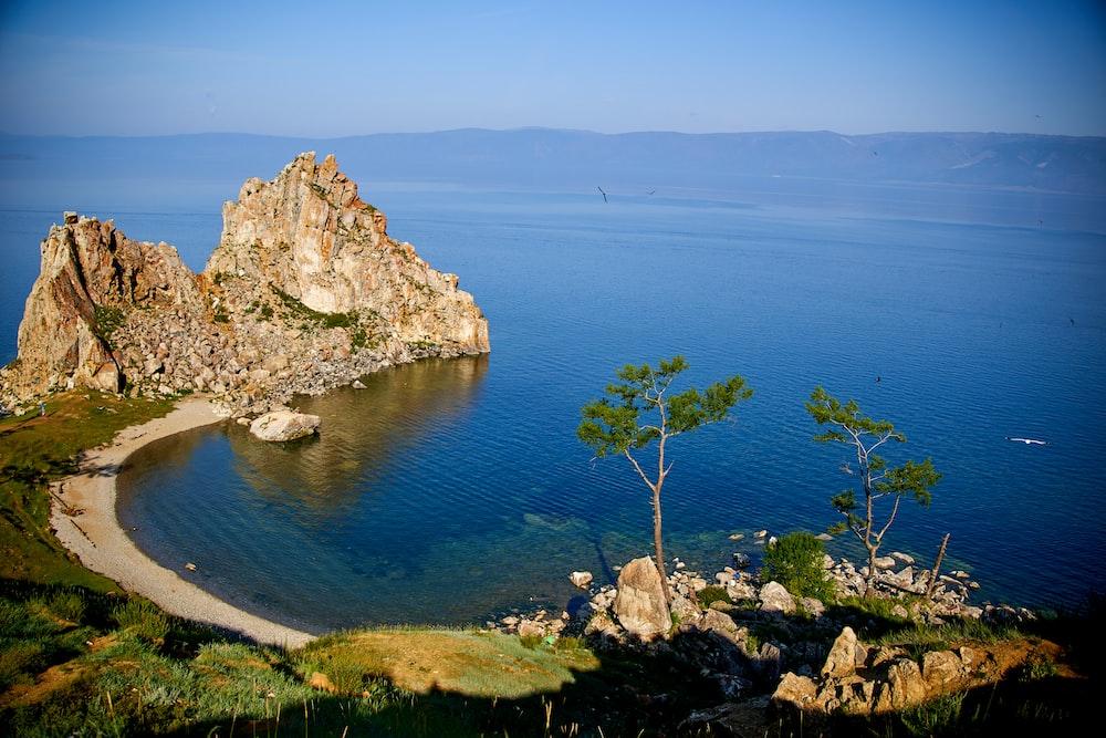 brown rock formation beside blue sea under blue sky during daytime