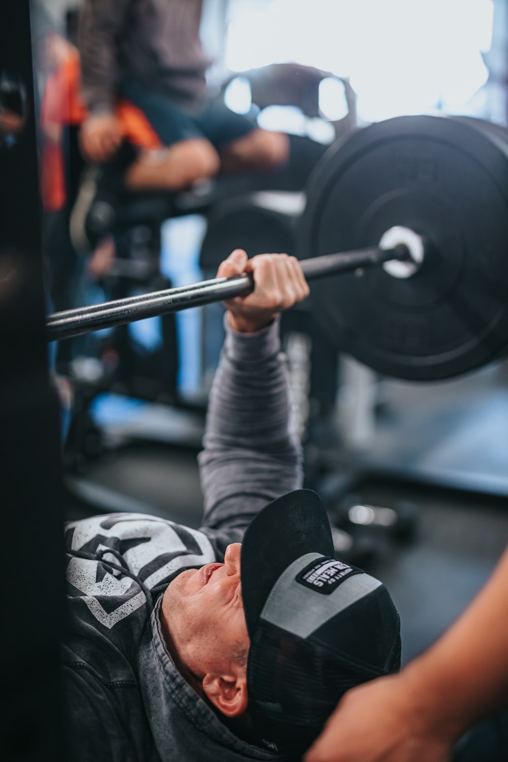 person in gray long sleeve shirt holding black barbell