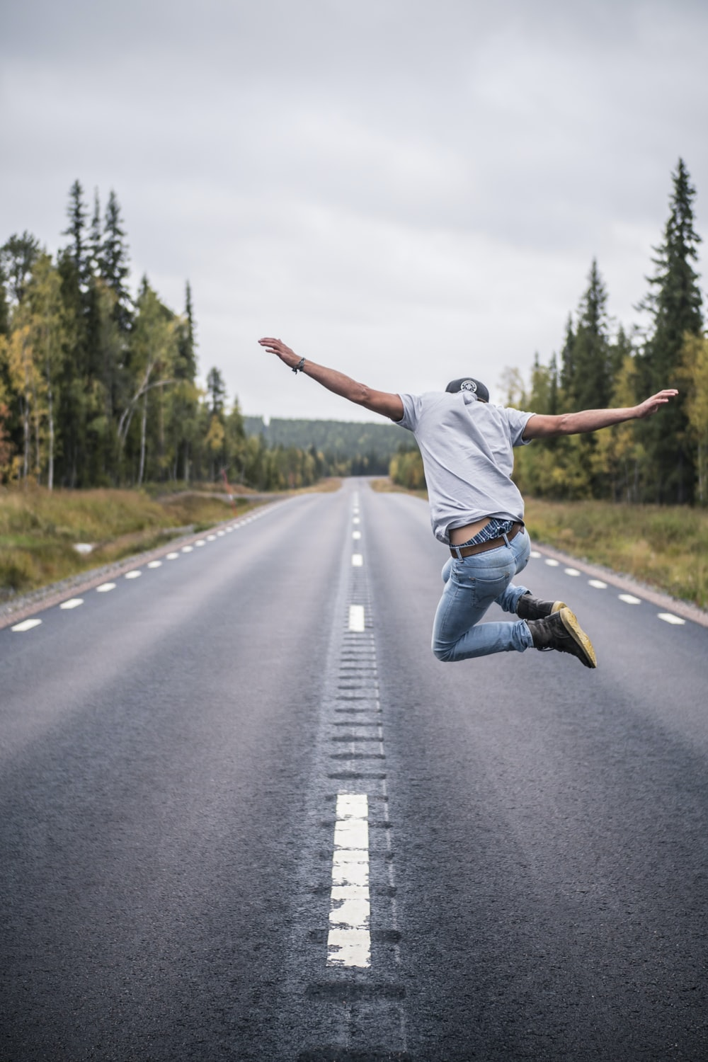 man in white t-shirt and blue denim jeans jumping on the road during daytime