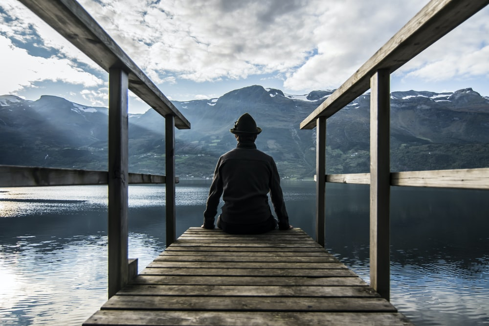 man in black hoodie sitting on wooden dock during daytime