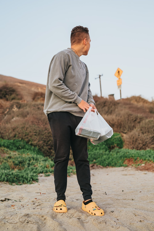 man in gray dress shirt and black pants holding white plastic bag