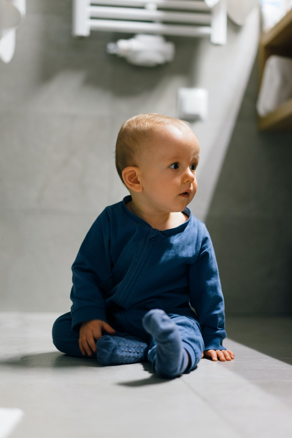baby in blue long sleeve shirt and blue denim jeans sitting on floor