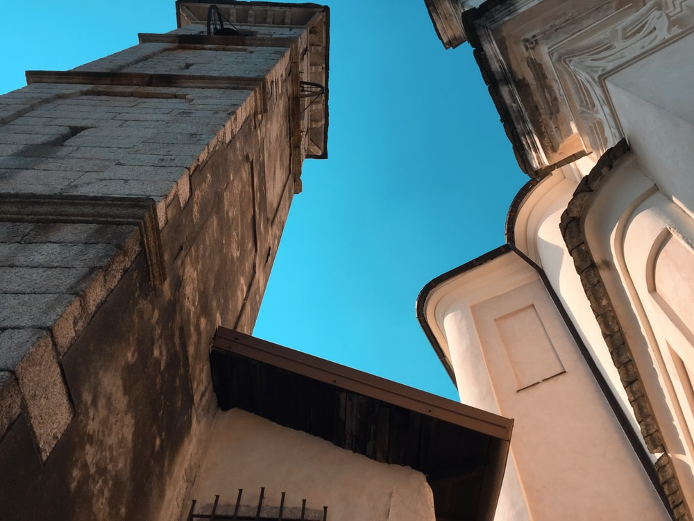 low angle photography of brown concrete building under blue sky during daytime