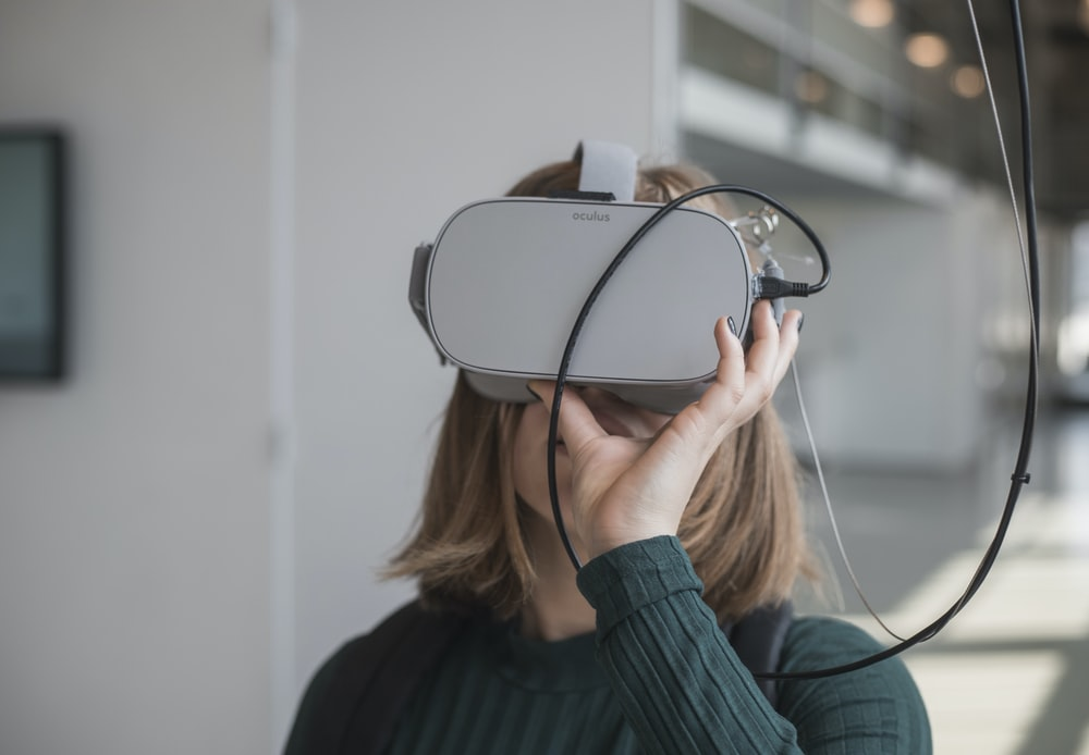 woman in black sweater holding white and black vr goggles