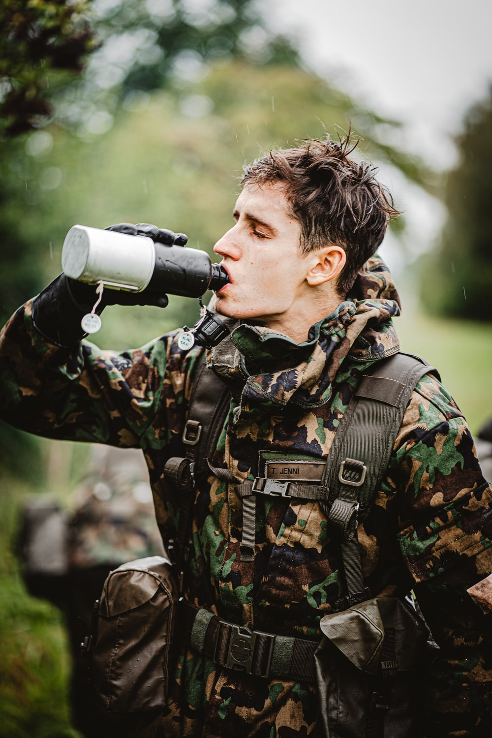 man in green and black camouflage jacket holding black and gray microphone