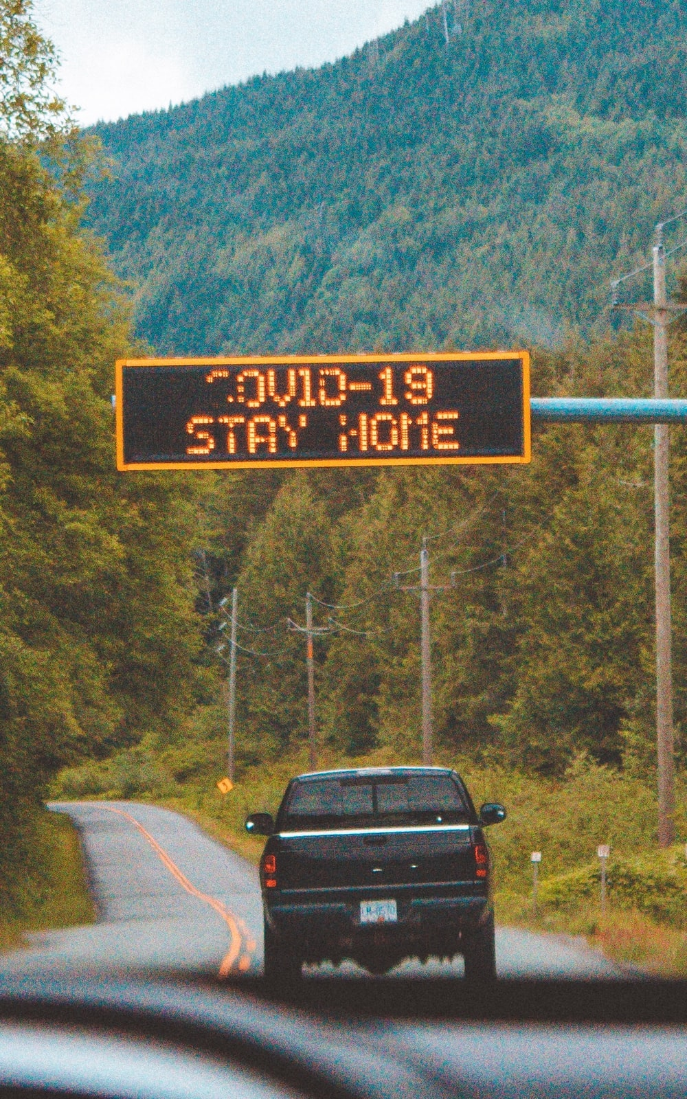 black car on road near the road sign