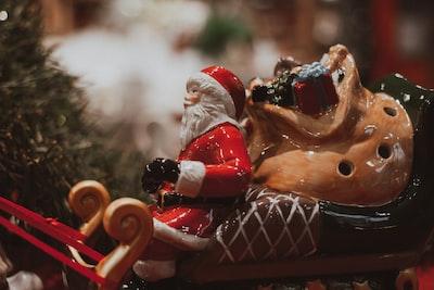 santa claus riding red car figurine sleigh zoom background