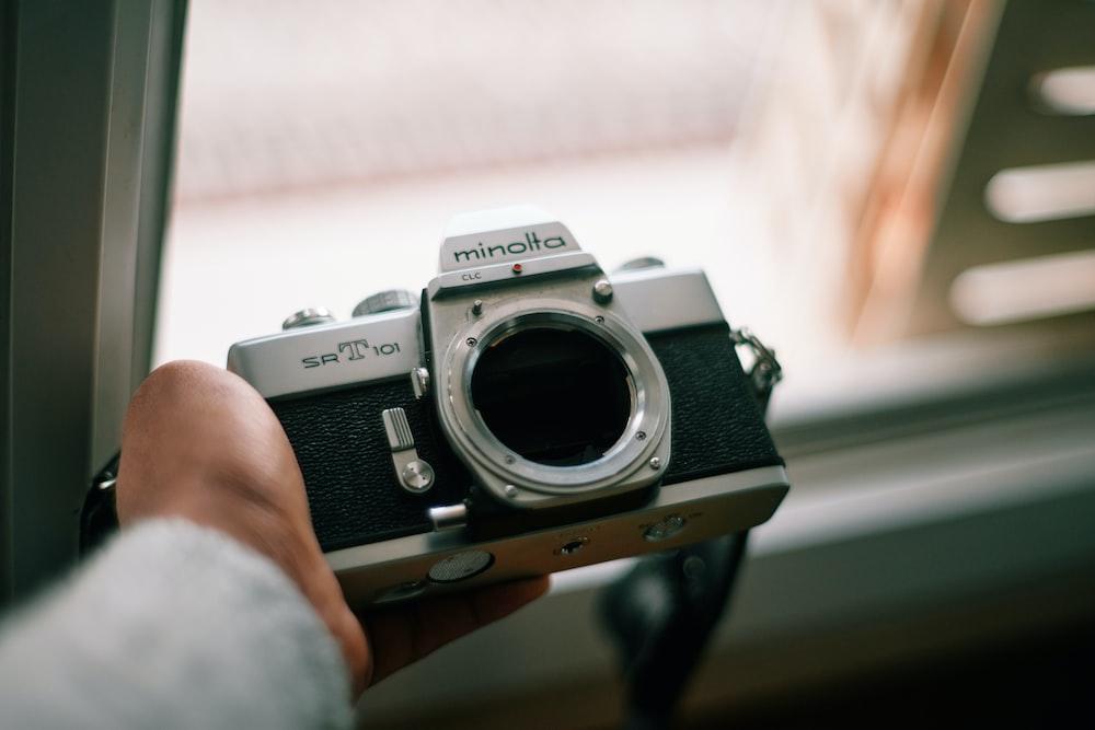 person holding gray and black canon dslr camera