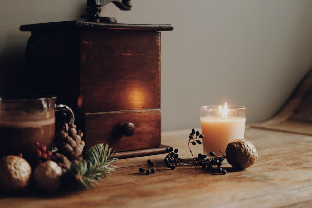 lighted candle beside brown wooden drawer