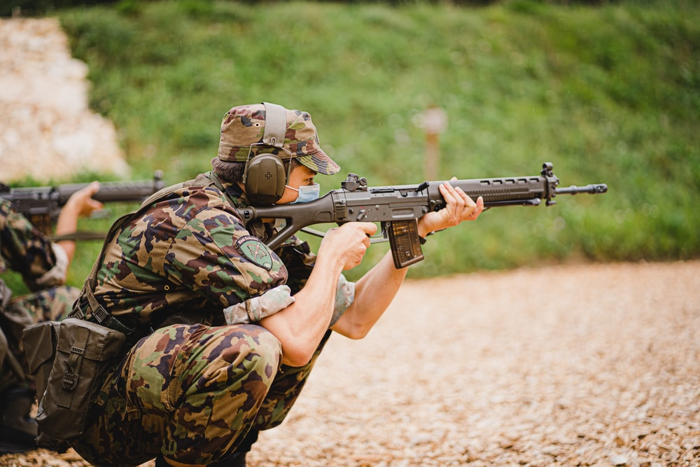 man in green and brown camouflage army suit holding rifle