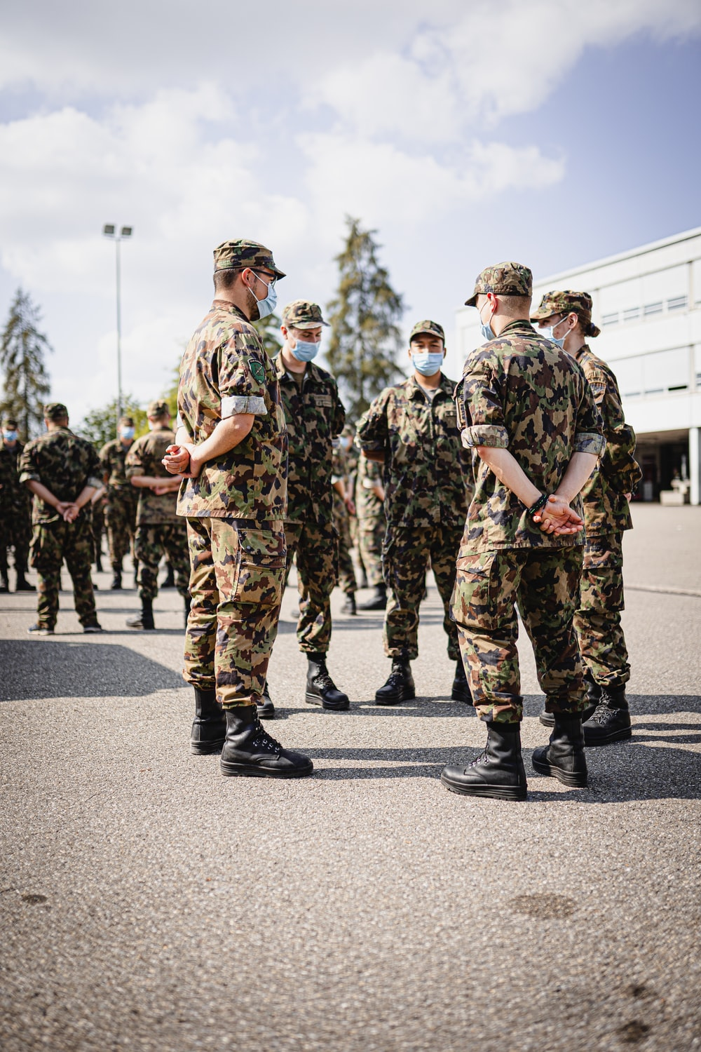 men in green and brown camouflage uniform standing on road during daytime