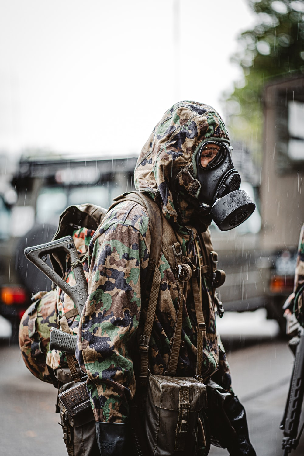 person in green and brown camouflage jacket wearing gas mask