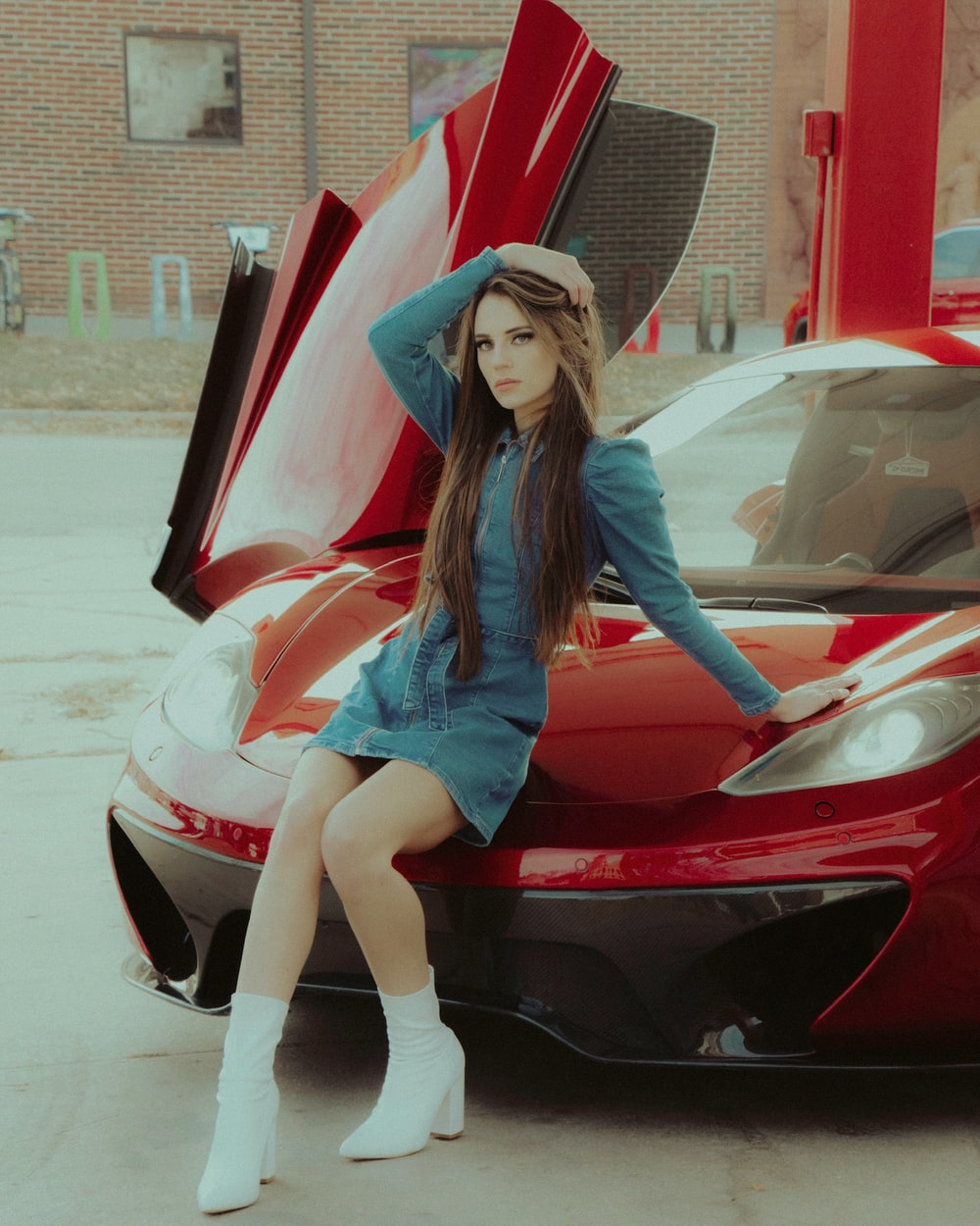 woman in blue long sleeve shirt and white denim shorts sitting on red car