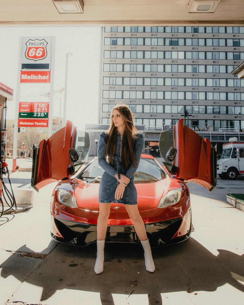 woman in black long sleeve shirt and blue denim jeans standing beside red ferrari car