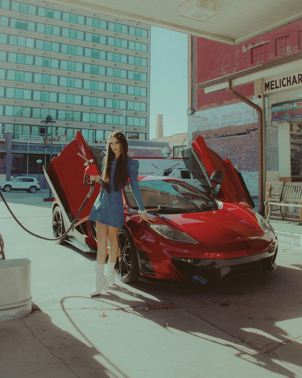 woman in blue dress standing beside red car during daytime