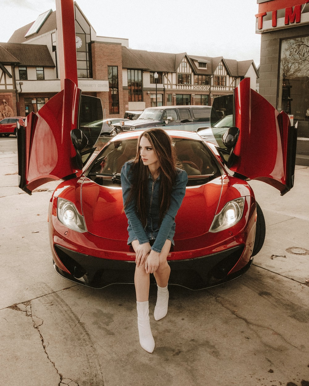 woman in blue jacket standing beside red car during daytime
