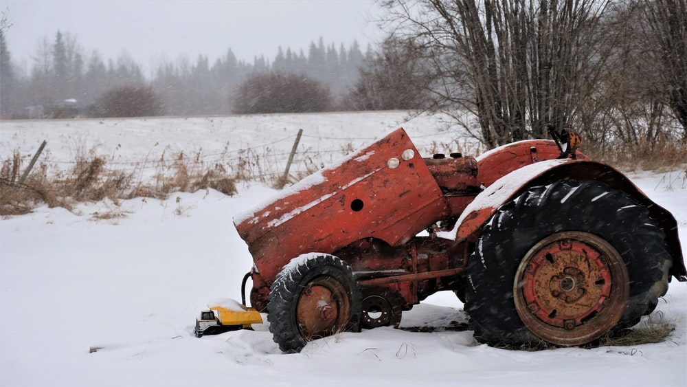 red tractor on snow covered ground during daytime