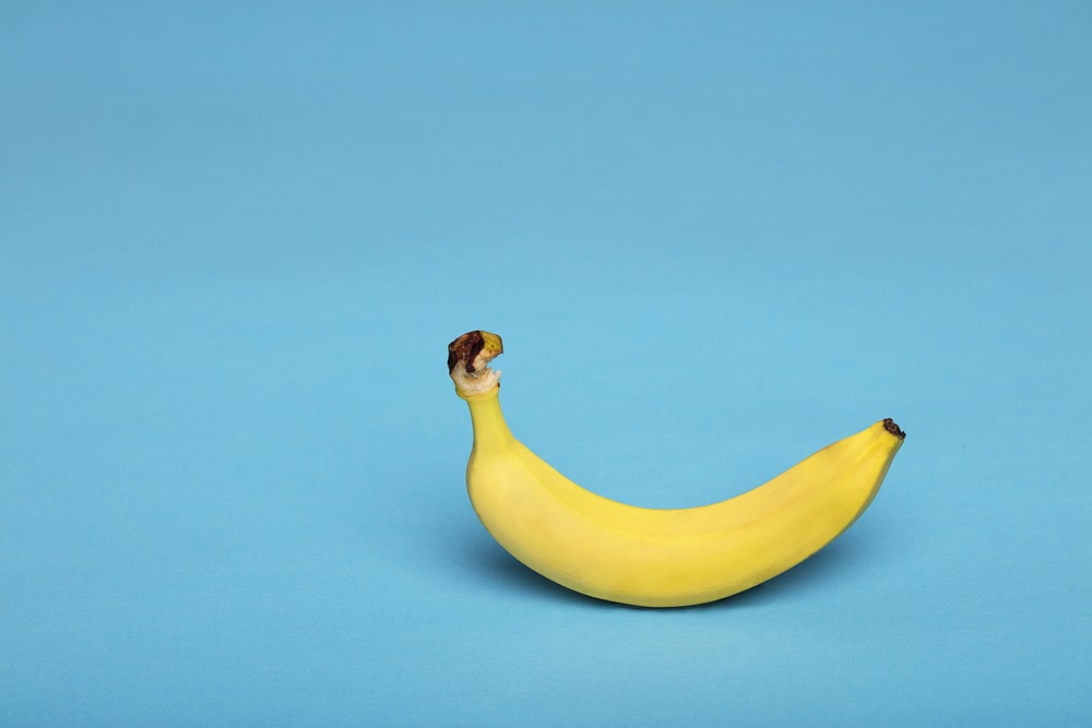 yellow banana fruit on blue surface