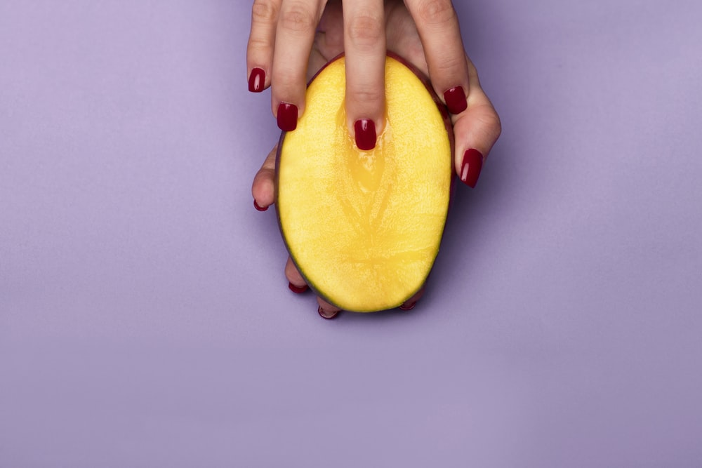 person holding sliced yellow fruit