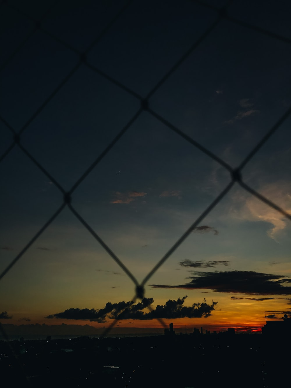 silhouette of chain link fence during sunset