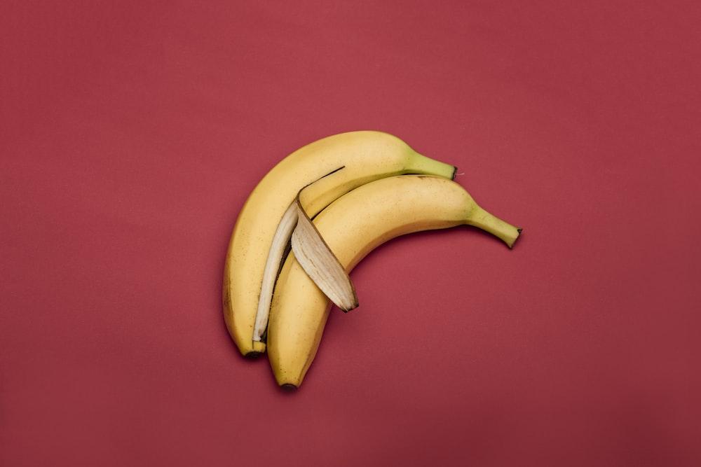 yellow banana fruit on red textile