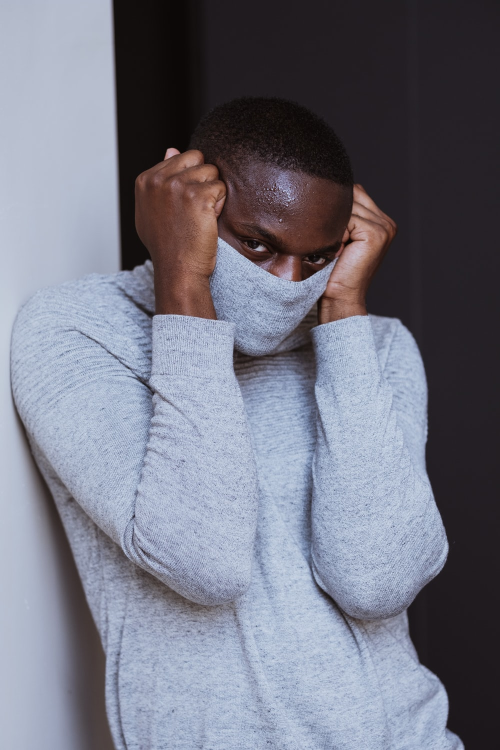 woman in gray sweater covering face with both hands