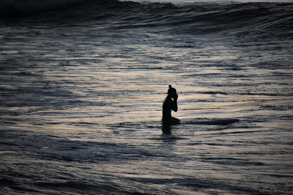 silhouette of woman standing on sea water during daytime
