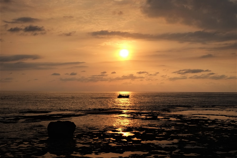 silhouette of rocks on sea during sunset