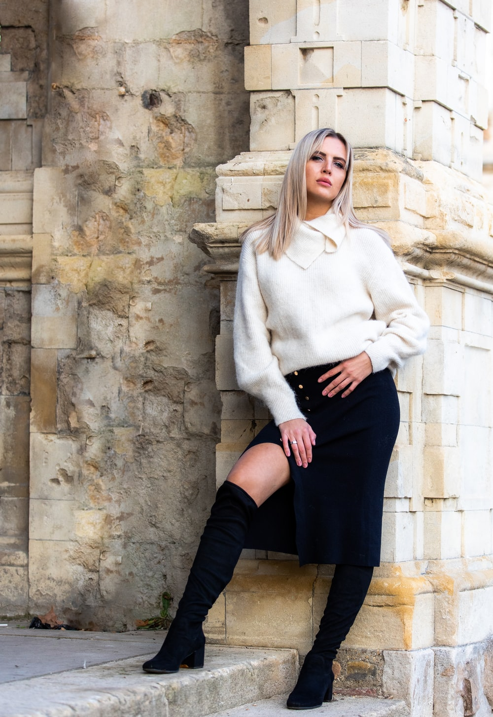 woman in white sweater and black skirt sitting on concrete wall during daytime