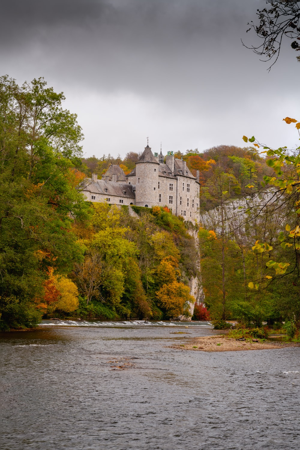 white and gray castle on green trees beside river during daytime