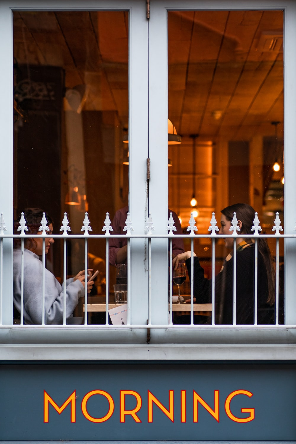 man in white dress shirt standing in front of glass window