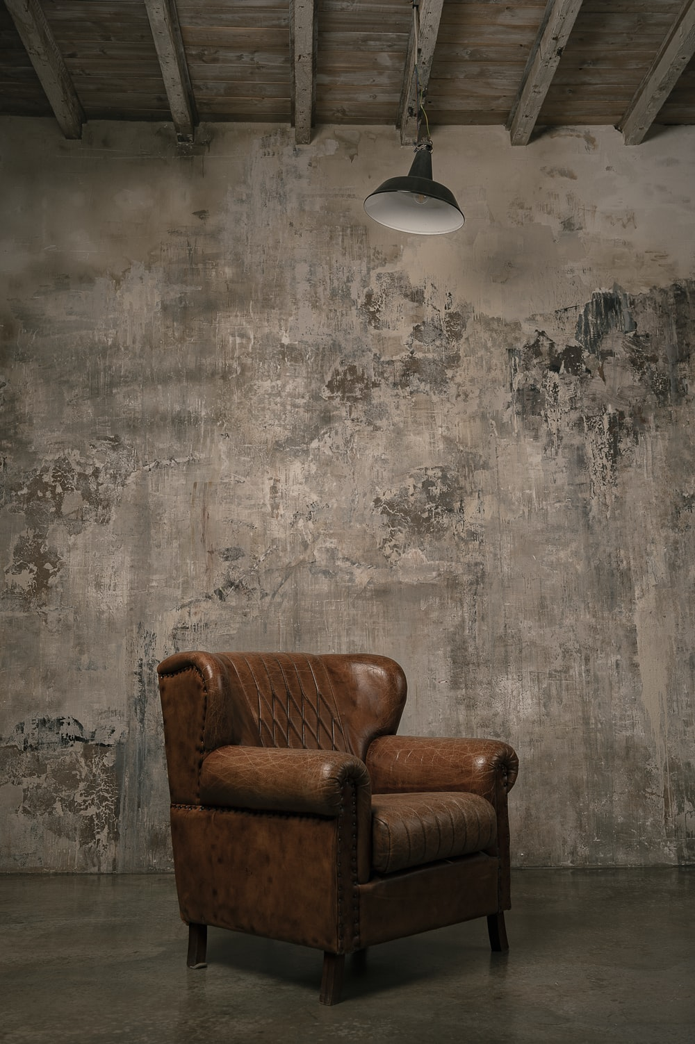 brown wooden armchair beside white wall