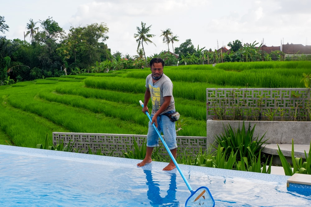 man in white polo shirt and blue denim jeans standing on swimming pool during daytime