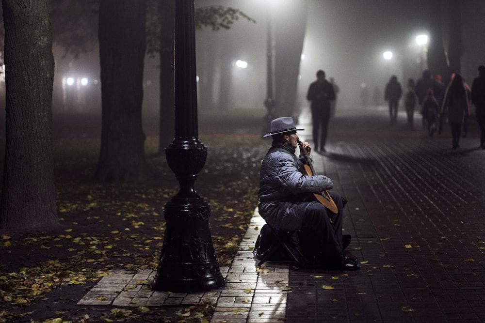 man in black jacket sitting on sidewalk during night time