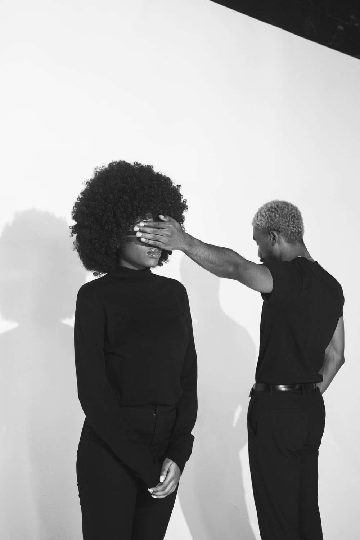 man in black shirt holding womans hair