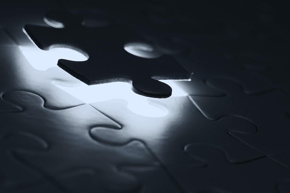 black puzzle piece on white paper