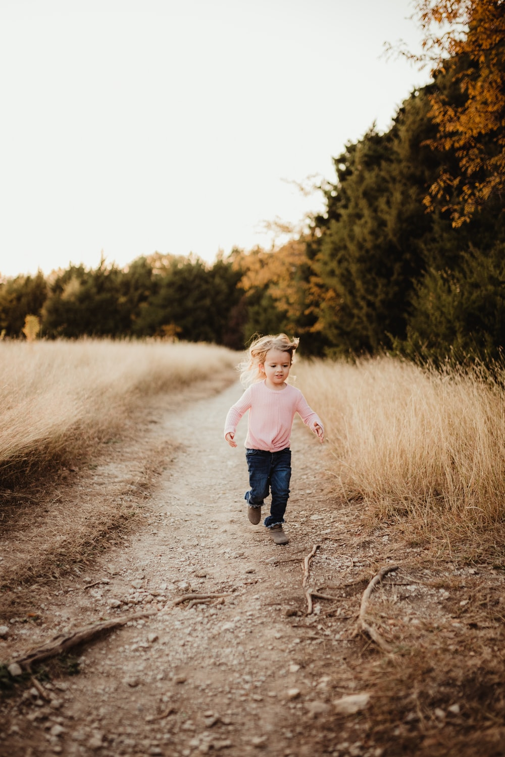 girl in white long sleeve shirt and blue denim jeans running on dirt road during daytime