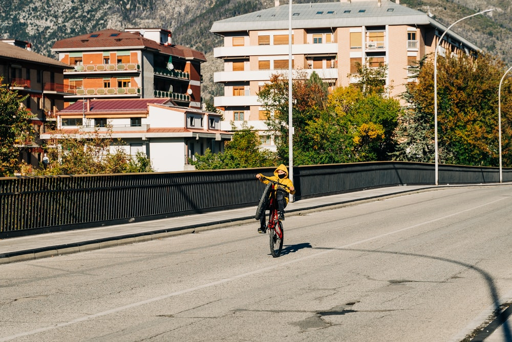 man in yellow jacket riding bicycle on road during daytime