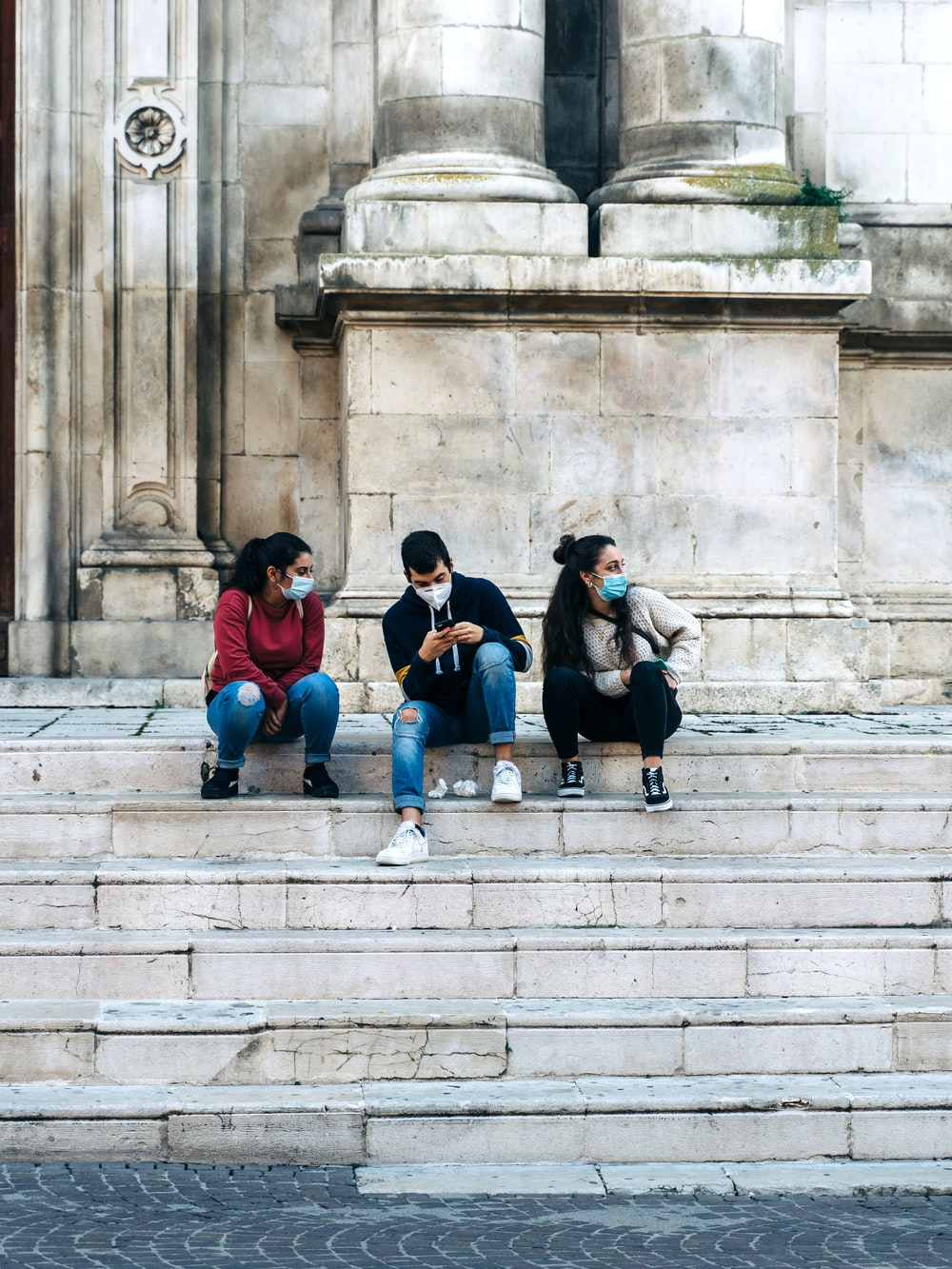 group of people sitting on concrete stairs