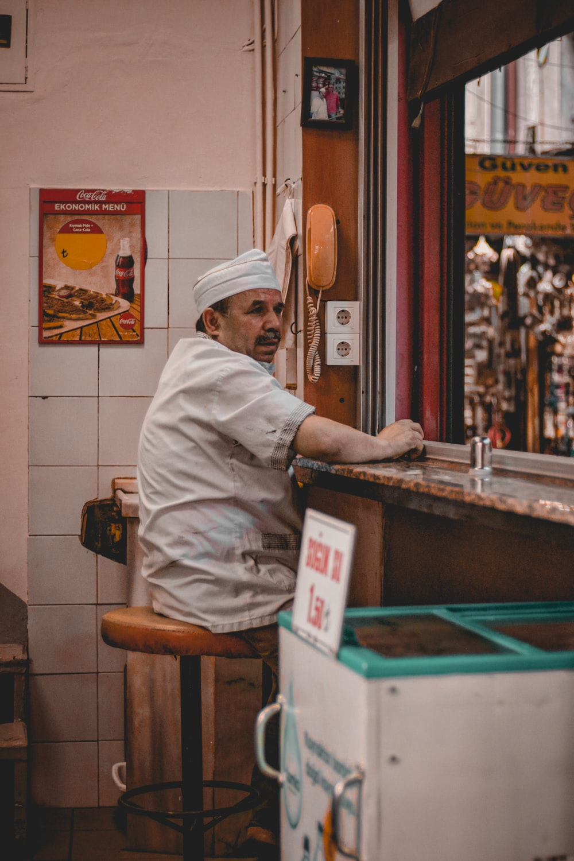 man in white chef uniform sitting on brown wooden chair
