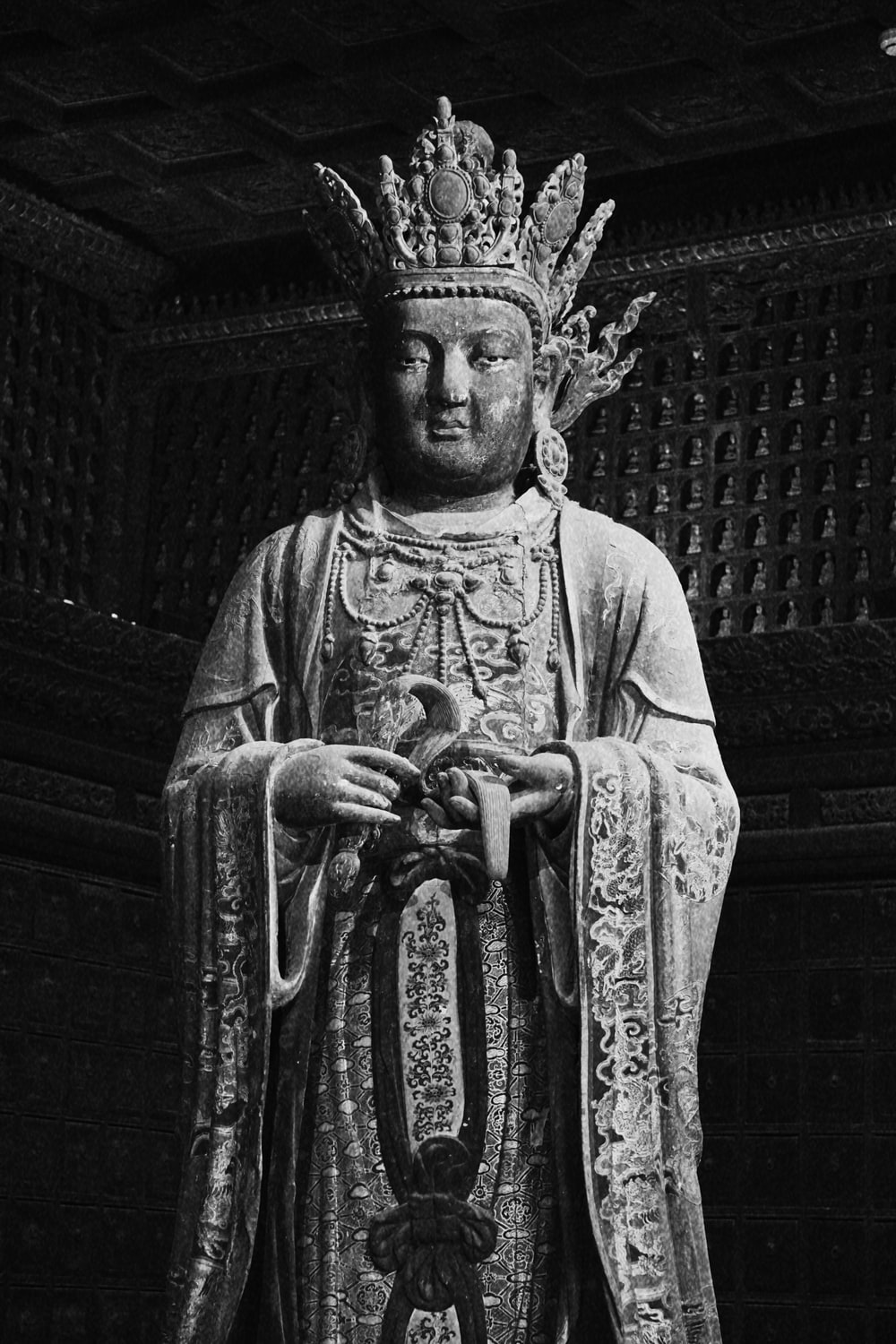 grayscale photo of man in robe statue